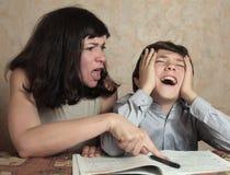 妈妈帮助儿子做difficul家庭作业 免版税库存图片