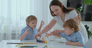 妈妈帮助她的儿子开发创造性的技能和与他们衔接在手指帮助下创造画的油漆 股票视频