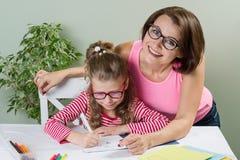 妈妈帮助她的在她的笔记本的女儿小学学生, 免版税库存照片