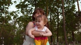 妈妈投掷空气的孩子在乐趣的街道上 婴孩嘲笑爱恋的妈妈的手 婴孩和妈妈笑,一起使用为 股票视频