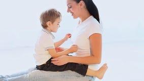 妈妈拥抱使用充满爱的年轻儿子 股票录像