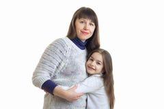 妈妈拥抱她的小女儿并且对照相机微笑 免版税库存照片
