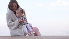 妈妈拥抱小女儿 观看在海滩的妈妈和女儿日落 股票录像