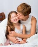 妈妈拥抱并且亲吻女儿 免版税图库摄影