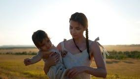 妈妈拿着她的站立在与草的一个干燥领域的儿子 影视素材