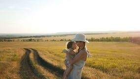 妈妈拿着她的站立在与草的一个干燥领域的儿子 股票视频