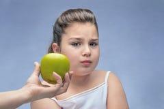 妈妈提供绿色苹果计算机对一个肥胖孩子 适当的营养拒绝  营养家长监督  肥胖病的问题 ?? 免版税库存图片