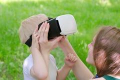 妈妈改正虚拟现实他的儿子玻璃以绿草为背景 免版税库存图片