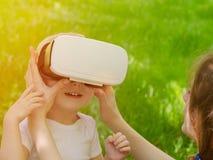 妈妈改正虚拟现实他的儿子玻璃以绿草为背景 库存照片