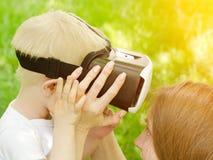 妈妈改正虚拟现实他的儿子玻璃以绿草为背景 免版税库存照片