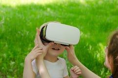 妈妈改正虚拟现实他的儿子玻璃以绿草为背景 库存图片