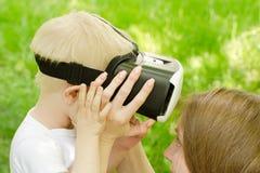 妈妈改正虚拟现实他的儿子玻璃以绿草为背景 免版税图库摄影
