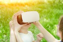 妈妈改正虚拟现实他的儿子玻璃  在背景的绿草 库存照片