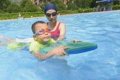 妈妈教的儿子学会在夏天游泳 库存图片