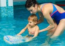 妈妈教婴孩游泳 免版税图库摄影