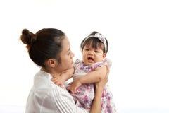 妈妈是举行和使用与她的婴孩 免版税库存图片