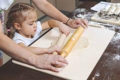 妈妈显示她女儿如何铺开做的饺子面团 免版税库存照片