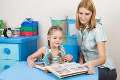 妈妈显示她的女儿家庭照片册页的五年 免版税库存照片