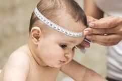妈妈测量头的大小一个美丽的婴孩 免版税库存照片