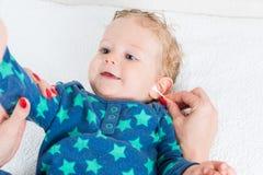 妈妈清洁有棉花棒的婴孩耳朵 免版税图库摄影