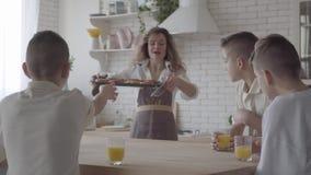 妈妈烘烤了小圆面包或饼干她的儿子的 家庭食用早餐在桌上在厨房 ?? ?? 影视素材