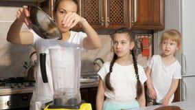妈妈烹调奶油使用有她的女儿的搅拌器在厨房里 股票视频