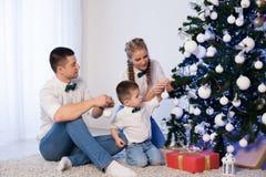 妈妈爸爸和一个小男孩装饰圣诞树在冬天 免版税图库摄影