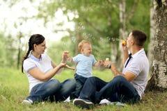 妈妈爸爸和婴孩在公园 免版税库存照片