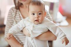 妈妈的胳膊的逗人喜爱的矮小的男婴空气的 母亲和婴儿,婴儿关心,儿童生长 感兴趣神色 免版税图库摄影
