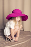 妈妈的鞋子和桃红色帽子的滑稽的小女孩 免版税图库摄影