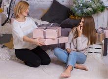 妈妈给礼物她的女儿 免版税库存图片