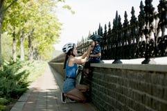 妈妈装备在自行车游览中的一个年轻儿子 免版税库存图片