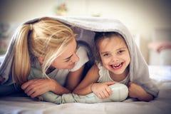 妈妈让皮在毯子,它下是滑稽的 免版税图库摄影