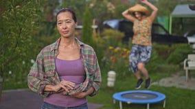 妈妈身分在庭院里,当她的女儿在绷床时跳 影视素材