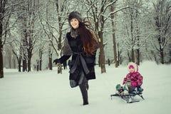 妈妈雪撬的辗压女儿在冬天公园 免版税库存图片