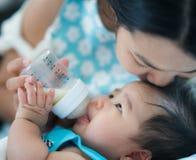 妈妈饲料对她的婴孩的力量英里 免版税库存照片