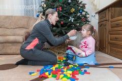 妈妈鼓励女儿吃张他的嘴,哺养与匙子,孩子坐罐 免版税库存照片