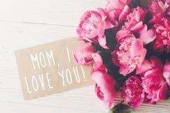 妈妈,我爱你在工艺卡片的文本和在r的桃红色牡丹花束 免版税库存图片