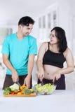 妊妇和丈夫准备沙拉 图库摄影