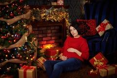 妊妇抚摸她的腹部在圣诞树 免版税库存照片