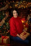 妊妇抚摸她的腹部在圣诞树 图库摄影