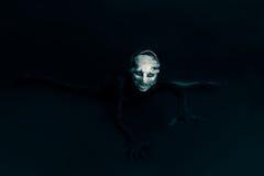 妖怪或外籍人爬行往您黑背景的 库存照片