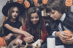 妖怪服装的三个孩子在万圣夜坐地板并且装饰鹿头骨 免版税库存照片