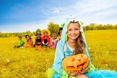 妖怪服装的女孩拿着万圣夜南瓜 免版税图库摄影