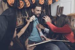 妖怪服装的孩子为万圣夜设法惊吓他们的有鹿头骨的父亲,但是他笑了 图库摄影