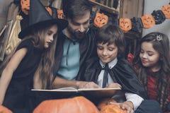 妖怪服装的孩子在一个黑斗篷的一个人附近坐并且读书在万圣夜党 库存照片