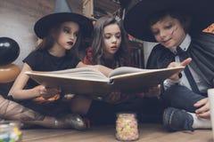 妖怪服装的孩子有兴趣的考虑spellbook 免版税库存照片