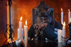 妖怪的图象的人有坐在与玻璃的桌手中,酒精上的垫铁的 库存照片