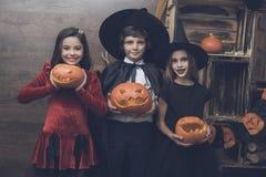 妖怪童话服装的三个孩子为举行在他们的手灯的万圣夜从南瓜雕刻了 图库摄影