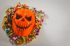 妖怪面具用在白色背景的各种各样的糖果 图库摄影